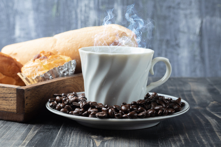 cup of hot coffee and roast coffee beans