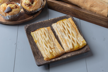 close up of bakery and pineapple pie on wooden board