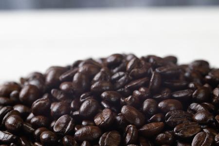 close up of pile roast coffee beans on wooden board Reklamní fotografie