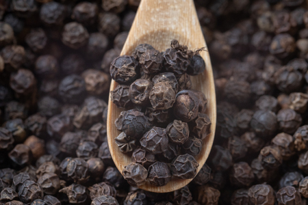 close up of pile black pepper and wooden spoon