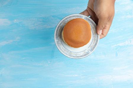 hand holding plate with dorayaki (Japanese Pancake Sandwich)