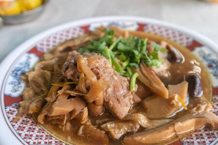 close up of Bak Kut Teh, stew of pork and herbal soup on bowl