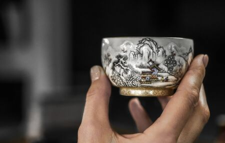 Ceramic cup for traditional chinese tea ceremony in a hand.