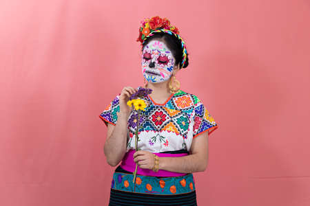 A young woman disguised as a catrina with a Mexican costume, posing with a plain background and flowers Standard-Bild
