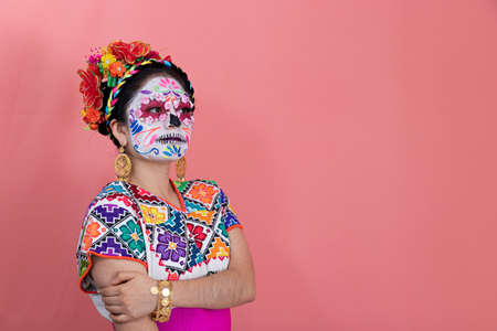 A young woman disguised as a catrina with a Mexican costume, posing with a plain background