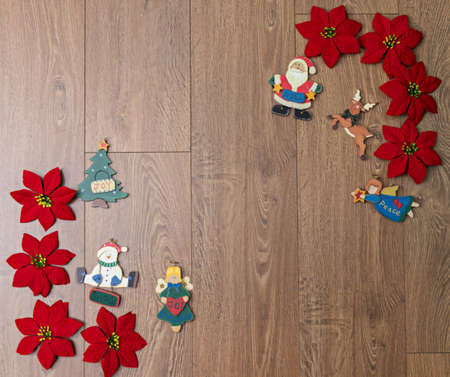 A wooden background with poinsettias and Christmas figures