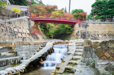 onsen: Japanese style public park  in autumn with little falls
