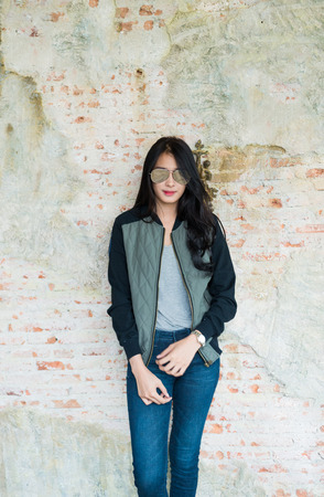 skinny jeans: Beautiful young woman in Skinny jeans against an old brick wall