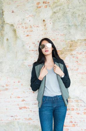 skinny jeans: Mujer joven hermosa en pantalones vaqueros pitillo contra un antiguo muro de ladrillo Foto de archivo