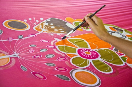 handicrafts: An artist carefully paint the floralflower motif on a red silk batik fabric