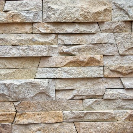 Uneven variety shape and texture of a stone wall for background photo