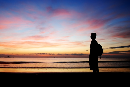 Silhouette of a man standing by the beach in the morning photo