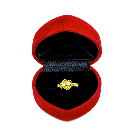 Gold wedding ring in a red heart shape box isolated on white background photo