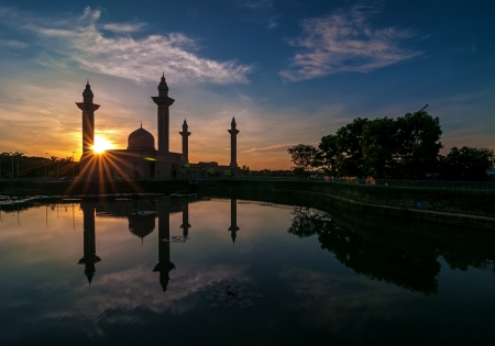Beautiful mosque at sunrise by the lakeside