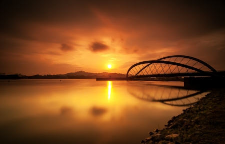 Curvy bridge in silhouette at sunrise in Putrajaya, Malaysia photo