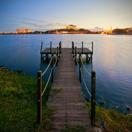 Landscape of Putrajaya lake with a jetty by the lakeside at sunset photo