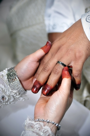 Malay bride putting a ring on groom finger