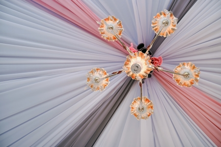 Beautiful decorative lamps hanging against colorful backdrop photo