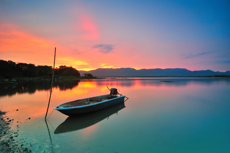 Lonely boat by the lakeside during beautiful sunset photo