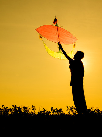 Kid playing a kite in silhouette photo