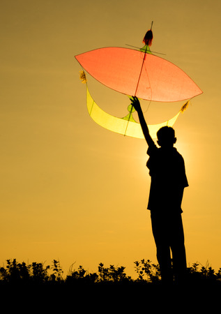A kid holding a kite in silhouette photo