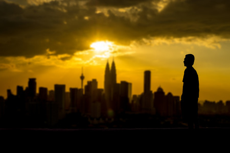 Silhouette of a man looking at the city from distance photo