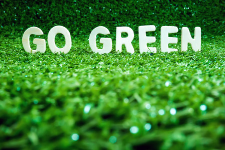 Eco concept. Go green wooden words on artificial grass (shallow depth of field) photo