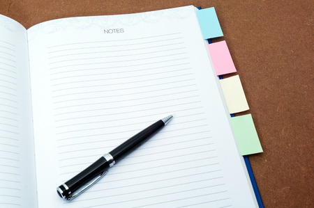 Blank notebook page with black ballpen and multi colored post it on wooden background Stock Photo