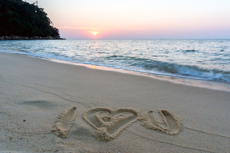 I love you symbol written on sandy beach at sunset photo