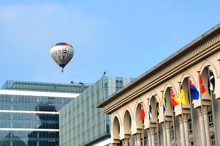 flew: PUTRAJAYA, MALAYSIA - MARCH 15, 2015 : A hot air balloon flew over Palace of Jusctice building during 7th Putrajaya International Hot Air Balloon Fiesta 2015 in Putrajaya, Malaysia