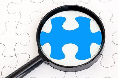 Concept image of missing puzzle pieces with magnifying glass showing the blank puzzle photo