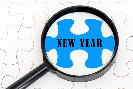 Concept image of missing puzzle pieces with magnifying glass showing the NEW YEAR word photo