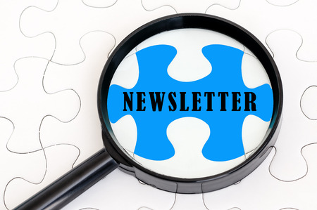 Concept image of missing puzzle pieces with magnifying glass showing the NEWSLETTER word photo