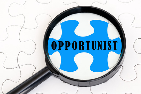 opportunist: Concept image of missing puzzle pieces with magnifying glass showing the OPPORTUNIST word