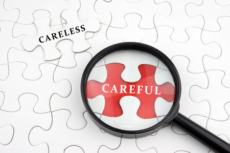 careless: Magnifying Glass On Missing Puzzle with CARELESS and CAREFUL Word, Antonym Concept, Selective Focus. Stock Photo