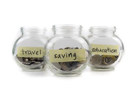 glass containers: Coins in glass containers with TRAVEL, SAVING and EDUCATION labels, on white background. Stock Photo