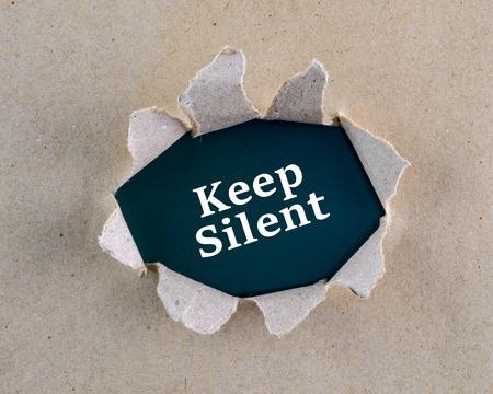 """guardar silencio: Torn papel con textura rugosa de color marrón con """"guardar silencio"""" palabras en la superficie de fondo. Foto de archivo"""