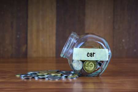 tax tips: Coins and glass container with Car label on wooden background.