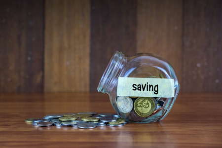 tax tips: Coins and glass container with Saving label on wooden background.