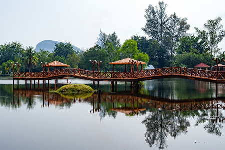 asian house plants: Beautiful garden with bridge and reflection in the lake Stock Photo