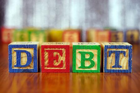 alphabet blocks: Word of DEBT spelled with colorful wooden alphabet blocks.