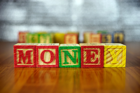 spelled: Word of MONEY spelled with colorful wooden alphabet blocks. Stock Photo