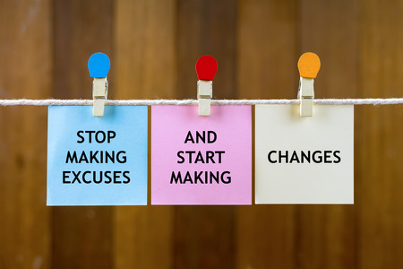 Word quotes of STOP MAKING EXCUSES AND START MAKING CHANGES on colorful sticky papers hanging by a rope against blurred wooden background. Stock Photo