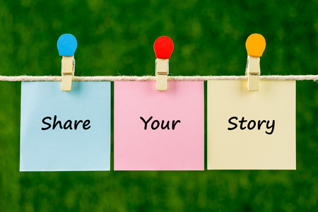 Words of Share Your Story on sticky color papers hanging by a rope against blurred green background.
