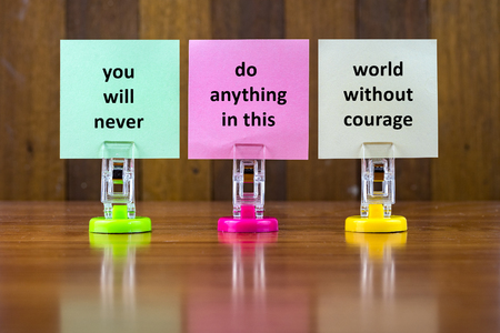 quotes: Word quotes of YOU WILL NEVER DO ANYTHING IN THIS WORLD WITHOUT COURAGE on colorful sticky papers against wooden textured background.