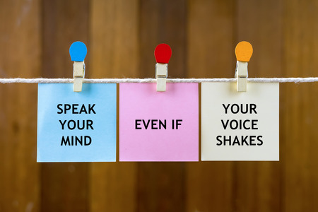 Word quotes of SPEAK YOUR MIND EVEN IF YOUR VOICE SHAKES on colorful sticky papers hanging by a rope against blurred wooden background.