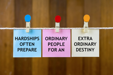 hardships: Word quotes of HARDSHIPS OFTEN PREPARE ORDINARY PEOPLE FOR AN EXTRA ORDINARY DESTINY on colorful sticky papers hanging by a rope against blurred wooden background. Stock Photo