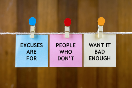 Word quotes of EXCUSES ARE FOR PEOPLE WHO DONT WANT IT BAD ENOUGH on colorful sticky papers hanging by a rope against blurred wooden background.