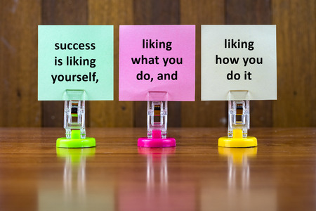 liking: Word quotes of SUCCESS IS LIKING YOURSELF,LIKING WHAT YOU DO,AND LIKING HOW YOU DO IT on colorful sticky papers against wooden textured background.
