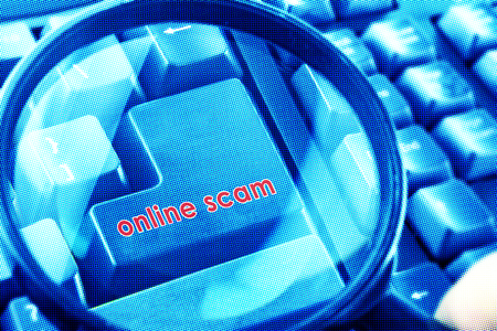 cyber terrorism: Magnifying glass on keyboard with Online Scam word on button. Color halftone effect applied.